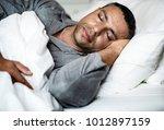 a man sleeping on a bed | Shutterstock . vector #1012897159