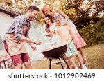 happy family having a barbecue... | Shutterstock . vector #1012902469