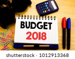 Small photo of Conceptual hand writing text caption showing Budget 2018. Business concept for Household budgeting accounting planning written on notebook book on the wooden background in Office with laptop coffee