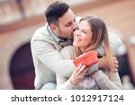 man giving a gift to his... | Shutterstock . vector #1012917124