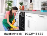 young woman cleaning oven in... | Shutterstock . vector #1012945636