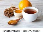 cup of tea served with orange... | Shutterstock . vector #1012975000
