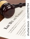 Small photo of Last will and testament on yellowish paper with wooden judge gavel; document is mock-up