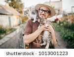 Stock photo happpy young bearded farmer holding two little kitten in hands outdoor in village with abstract 1013001223
