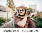 Stock photo happpy young bearded farmer holding two little kitten in hands outdoor in village with abstract 1013001226