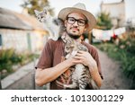 Stock photo happpy young bearded farmer holding two little kitten in hands outdoor in village with abstract 1013001229