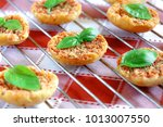 Small photo of Close up of Mini pizas baked with tomato, oregano and basil on red and white checkered table coth