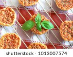 Small photo of Mini pizas baked with tomato, oregano and basil on red and white checkered table coth.