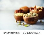 pistachios nuts in wooden bowl. ... | Shutterstock . vector #1013039614