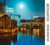 Small photo of spree river at night in berlin with bode museum on the side