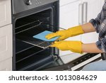 woman cleaning oven in kitchen  ... | Shutterstock . vector #1013084629