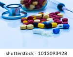 Small photo of top view color drug contain blue pills, yellow-red or capsules on a white background with copied clearance. Medication in healthy containers, antibiotics and dangerous drugs.