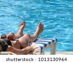 slim girl sunbaths on a lounger ... | Shutterstock . vector #1013130964