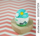Small photo of Cute kid hand painted easter egg on a red chevron background wit