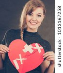 Small photo of Healed love. Valentines Day concept. Young smiling woman holding big red heart with plaster. Girlfriend healing relationship.