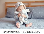 Stock photo portrait of cute adorable caucasian blonde smiling baby girl with blue eyes in grey pajama with fox 1013316199