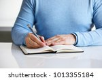 a man writes a black diary... | Shutterstock . vector #1013355184