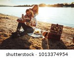 a young couple having a picnic... | Shutterstock . vector #1013374954