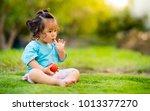 little girl eating tomato on... | Shutterstock . vector #1013377270
