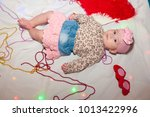 Small photo of Beautiful baby girl in skirt, pink bow laying near red heart glasses and feather veer, beads on white background