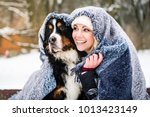 Stock photo woman and her dog getting warm on cold winter day under a blanket snuggling 1013423149