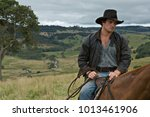 Man on horse in countryside - stock photo