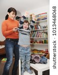mother helping son get dressed | Shutterstock . vector #1013468068