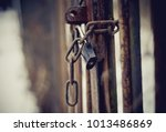 a metal gate closed on the lock ... | Shutterstock . vector #1013486869