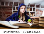 teenage girl in a library | Shutterstock . vector #1013515666
