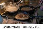 prepares pancakes in the kitchen | Shutterstock . vector #1013519113