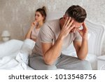 sad man sitting on bed with his ...   Shutterstock . vector #1013548756