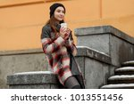 Stock photo student girl drinking coffee during a break and breathing air good combination of plaid coat and 1013551456