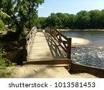 bridge crossing the rushing... | Shutterstock . vector #1013581453