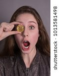 Small photo of Girl amateur bitkoynov with a gold coin in his eyes.