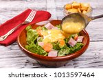 pouring dressing on a salad. | Shutterstock . vector #1013597464