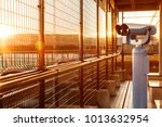 Small photo of coin-operated binoculars or telescope in the morning golden glowing light for tourists to observe plane takeoffs and ladings in airport observation deck with copy space