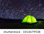 glowing green camping tent on... | Shutterstock . vector #1013679538