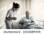nurse giving senior woman...   Shutterstock . vector #1013689444