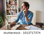 young man sitting at a table in ...   Shutterstock . vector #1013717374