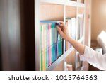 choosing a book in the library. | Shutterstock . vector #1013764363