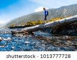 woman hiker crossing the... | Shutterstock . vector #1013777728