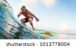 young surfer rides ocean wave... | Shutterstock . vector #1013778004