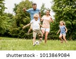 active family play soccer in... | Shutterstock . vector #1013869084