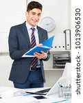 Small photo of Businessman is signing agreement papers of financial nature at office.