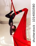 Small photo of Beautiful aerialist girl doing acrobatic and flexible tricks on red aerial silks (tissues) on white brick and white wall on background