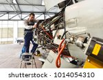 aircraft mechanic repairs an... | Shutterstock . vector #1014054310