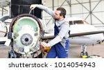 aircraft mechanic repairs an... | Shutterstock . vector #1014054943