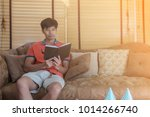 Small photo of Man have relax time with sit on brown vintage sofa and read book with light leak