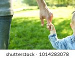 the parent holds the hand of a... | Shutterstock . vector #1014283078