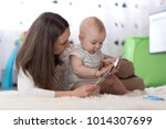 mother showing images in book... | Shutterstock . vector #1014307699